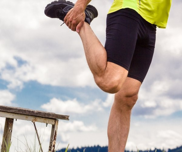 Man stretching his quadriceps before a run in a field.