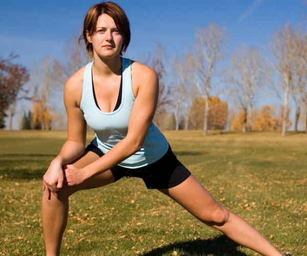 Woman stretching her groin whilst in a field.